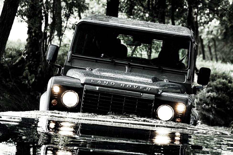 Land Rover Defender wading through a pond